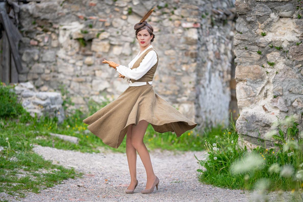 RetroCat beim Tanzen in einem nostalgischen Outfit bestehend aus Rock und passender Weste sowie einem Fascinator