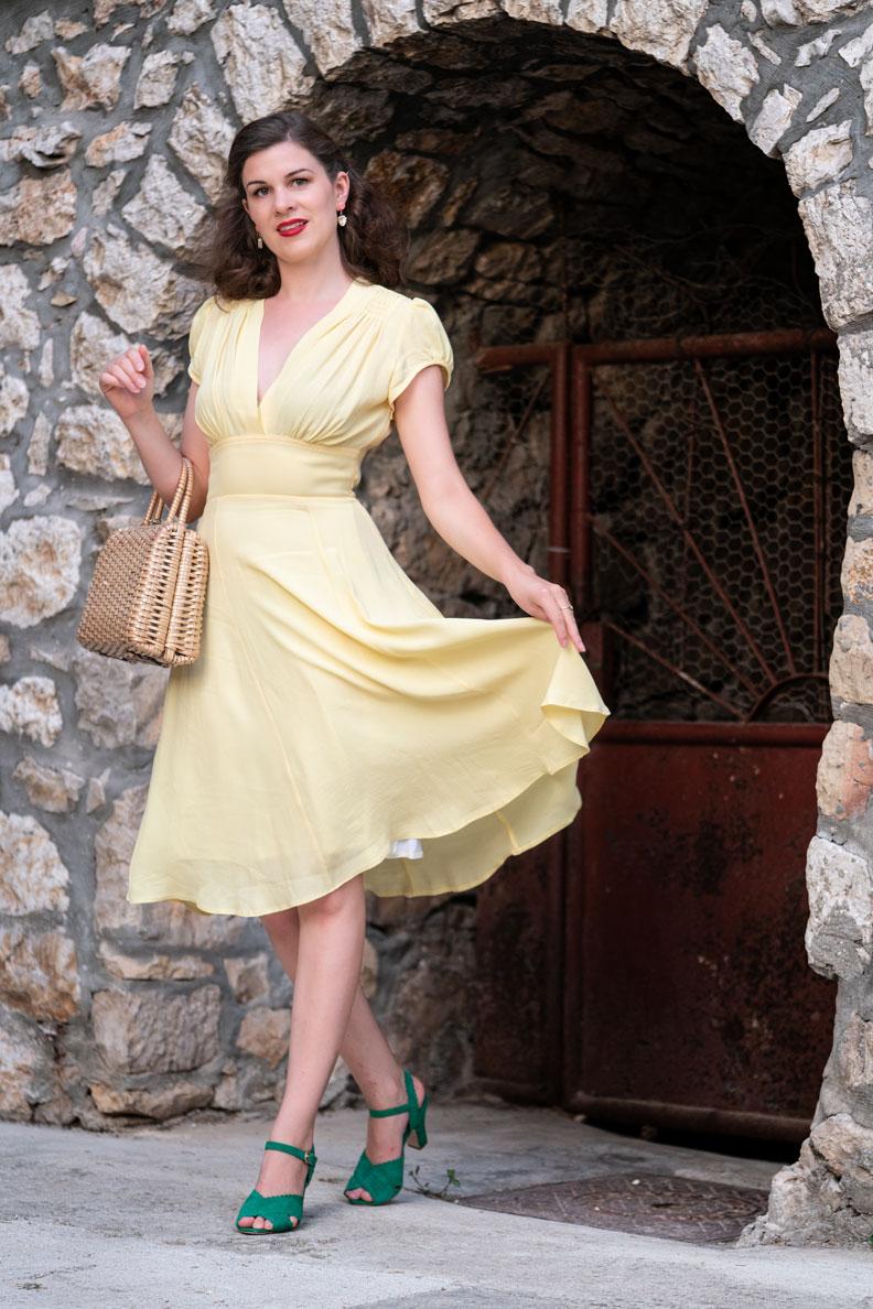 RetroCat in einem luftigen Retro-Sommerkleid in Hellgelb sowie passenden Vintage-Accessoires