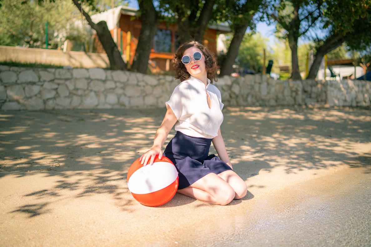 RetroCat mit einem Retro-Strand-Outfit, Wasserball und Sonnenbrille am Meer