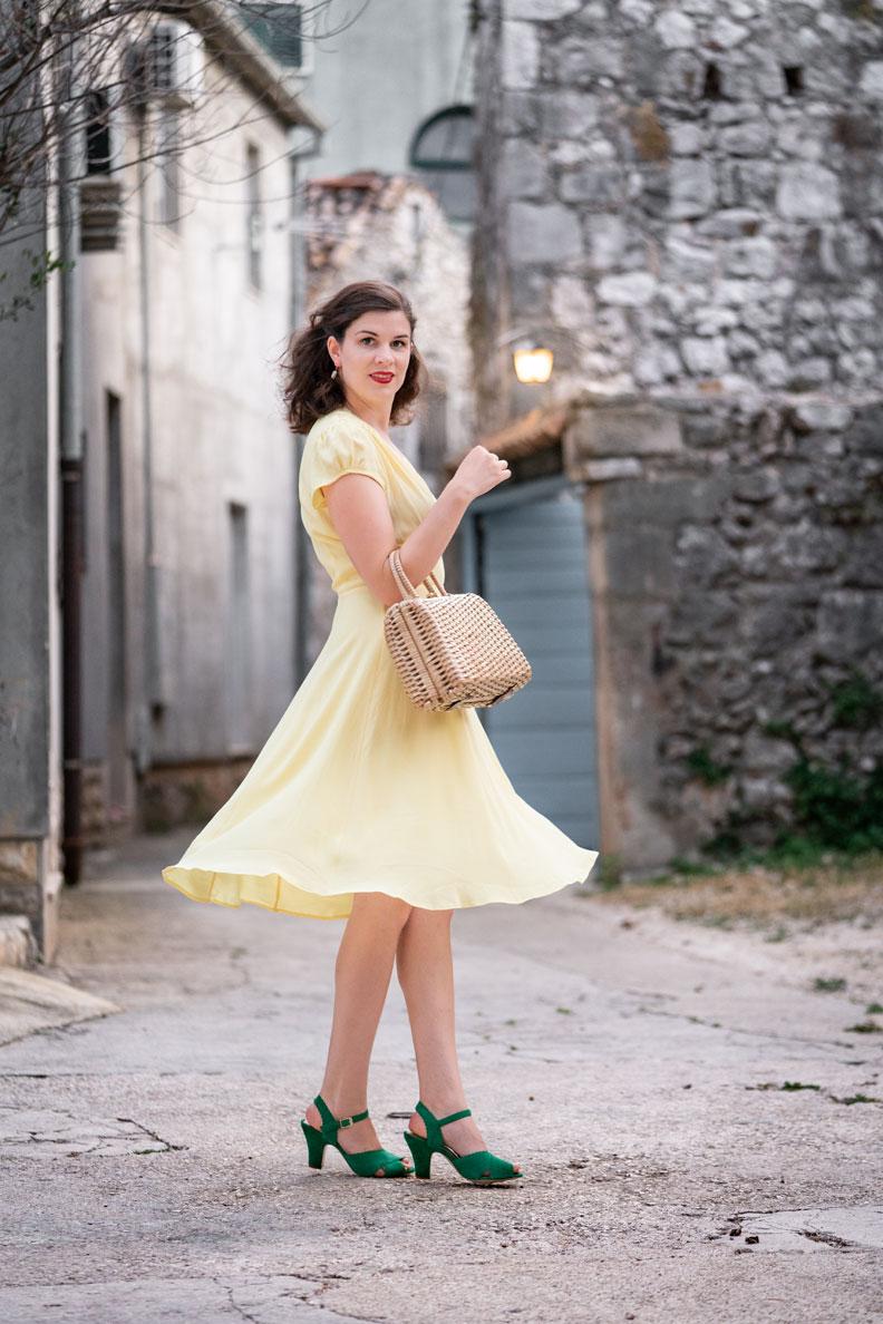Vintage-Fashion-Bloggerin RetroCat mit einem gelben Sommerkleid in der Stadt