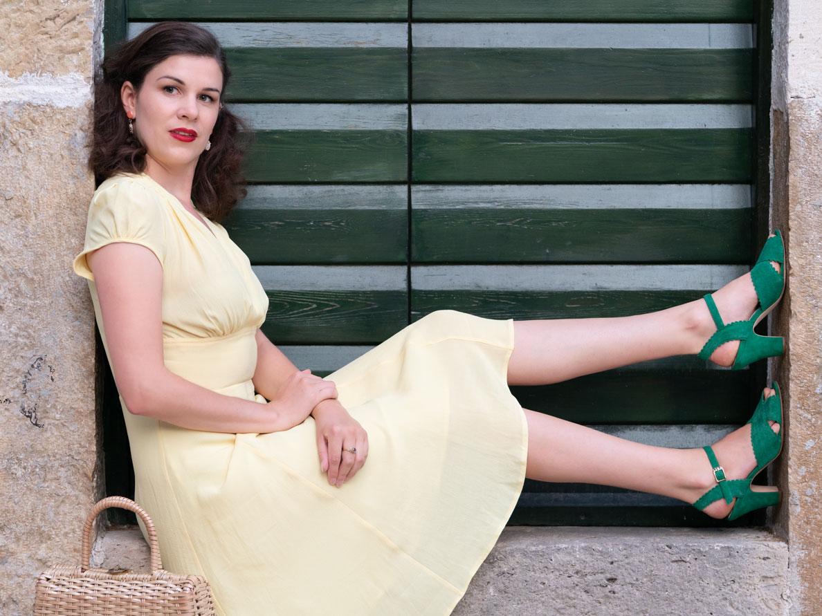 RetroCat in einem gelben Sommerkleid von The House of Foxy via Mondo Kaos vor einer grünen Tür