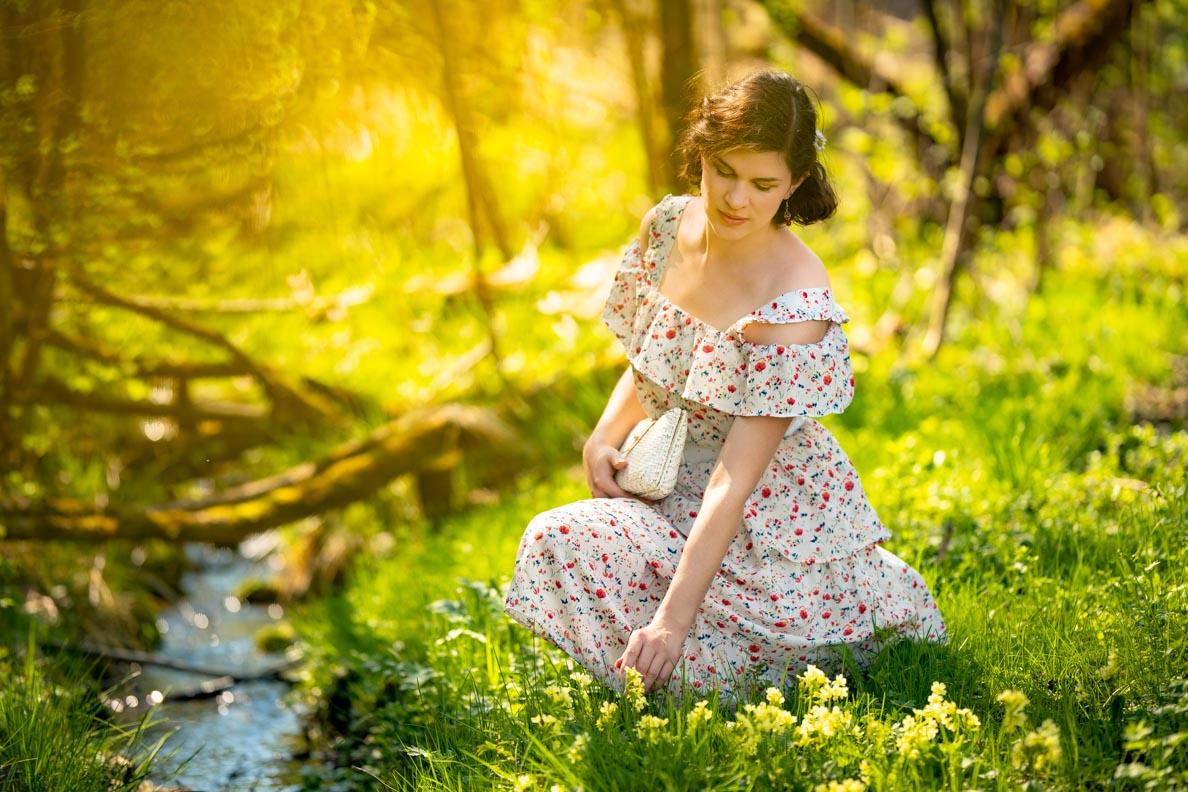 RetroCat in einem langen Kleid mit Boho-Elementen in einer Blumenwiese