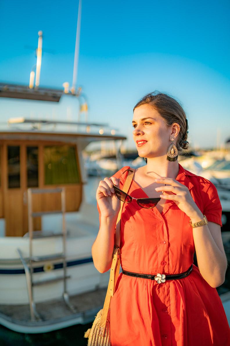 RetroCat mit Ethno-Ohrringen und einem orangen Kleid im Sommer-Urlaub