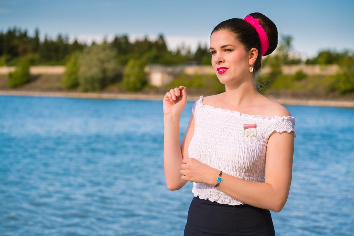 RetroCat mit Muschel-Ohrringen, weißem Top und pinkem Lippenstift