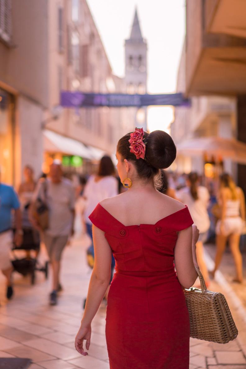 RetroCat mit einem roten Kleid, großem Dutt und einer Haarblume in Zadar