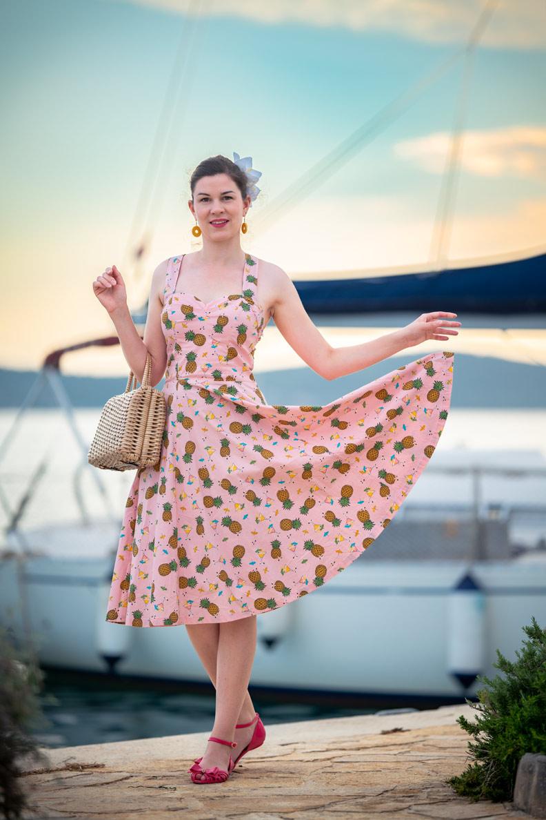 RetroCat mit einem rosa Ananas-Kleid, Korbtasche und passenden Accessoires