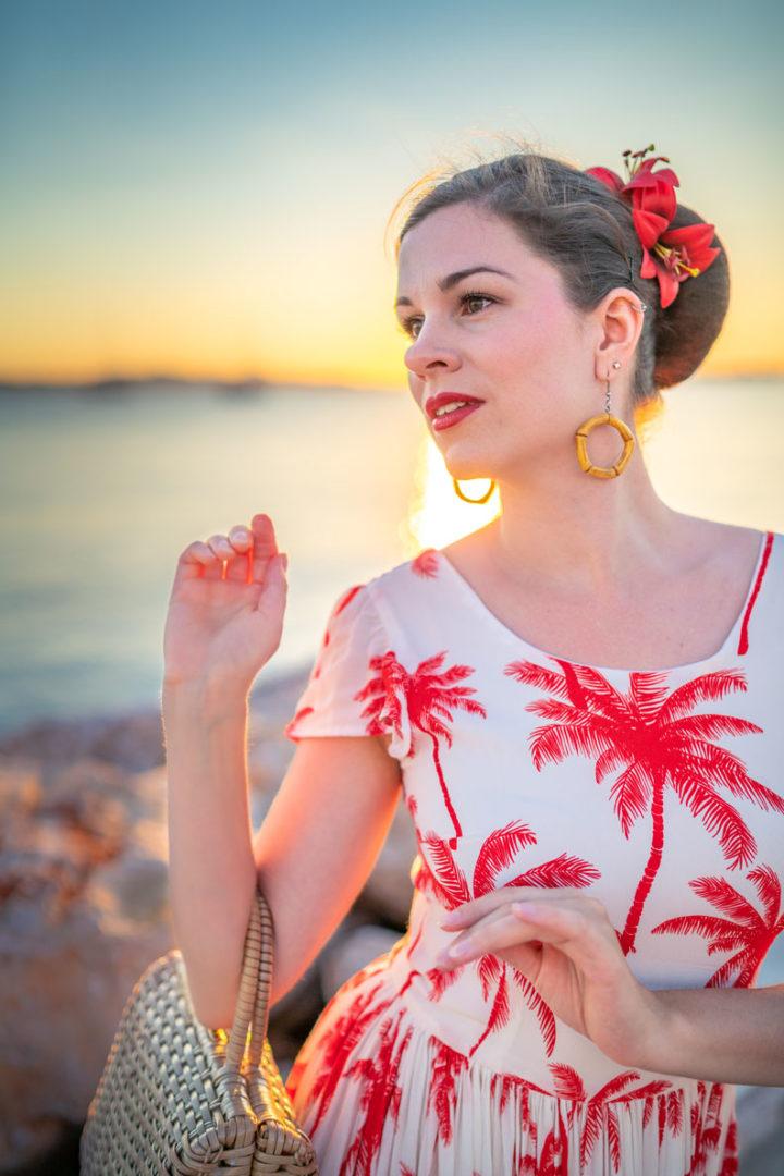 RetroCat mit Palmen-Kleid, Bambus-Ohrringen und einer Haarblume im Sommerurlaub