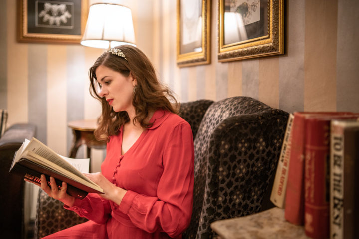 Schottland Packliste für Outfits: RetroCat im roten Kleid beim Lesen in Inverness