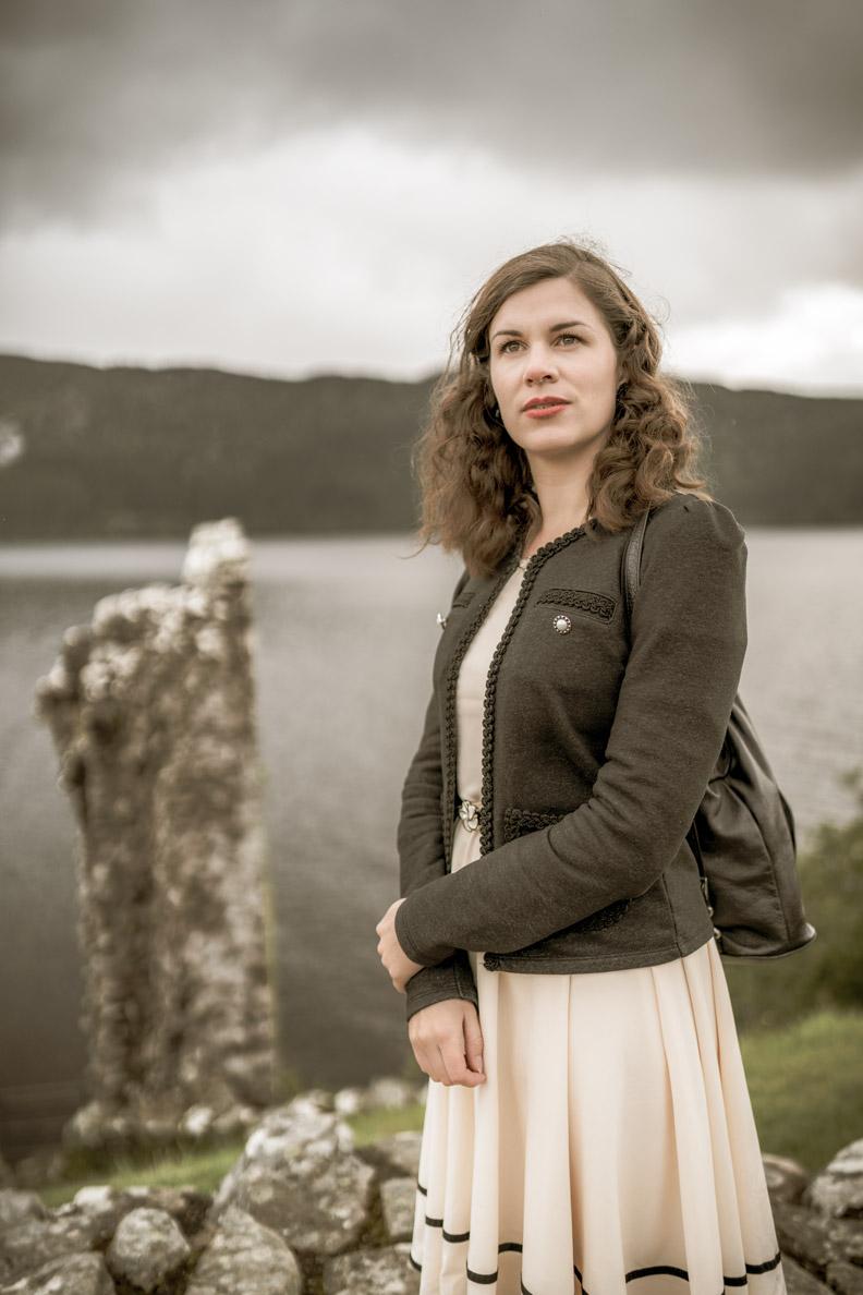 RetroCat mit beigem Kleid und schwarzer Jacke auf Urquhart Castle am Loch Ness/Schottland