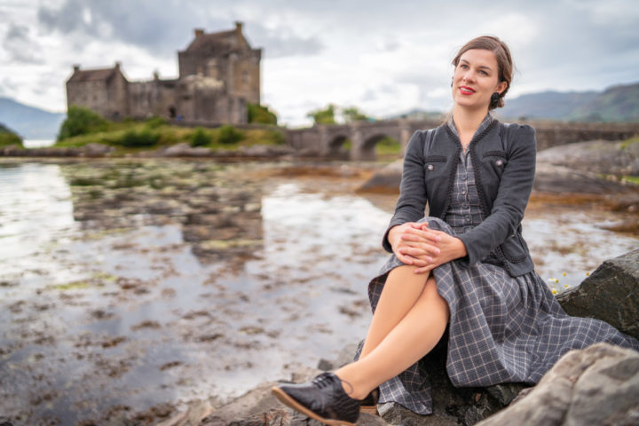 Schottland Packliste für Outfits: RetroCat mit kariertem Kleid vor dem Eilean Donan Castle