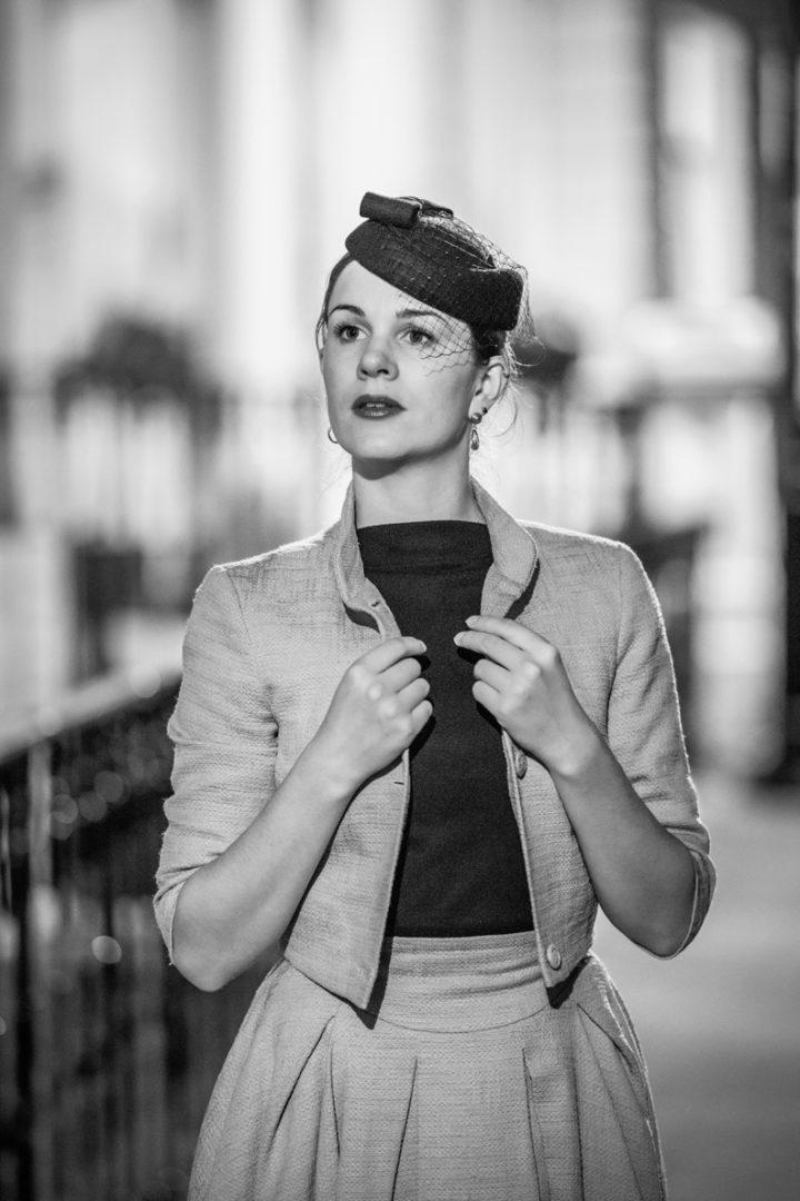 Vintage-Bloggerin RetroCat mit schwarzem Hut und heller Jacke in Glasgow/Schottland