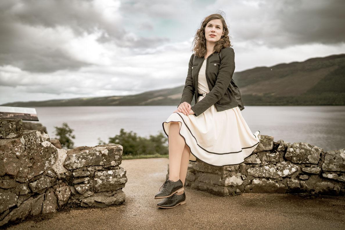 Schottland Packliste: RetroCat mit beigem Kleid und Schuhe im Stil von Clair Fraser aus Outlander am Loch Ness