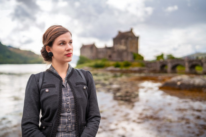 Fashion-Bloggerin RetroCat mit Karo-Kleid und Strickjacke vor dem Eilean Donan Castle in Schottland