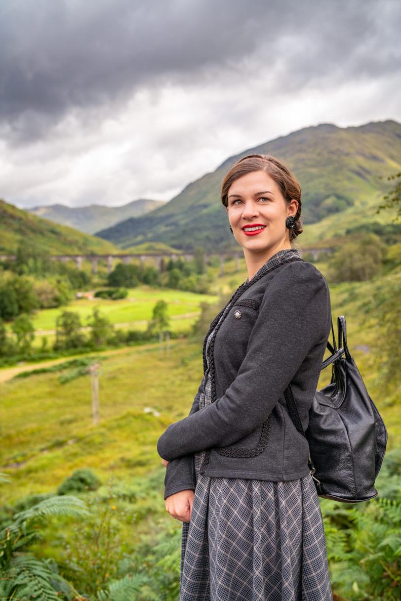 Mode-Bloggerin RetroCat mit Karo-Kleid und Strickjacke am Glenfinnan Viadukt