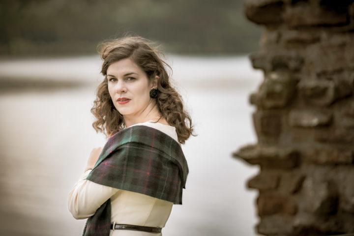 RetroCat mit lockigem Haar, beigem Kleid und Schal inspiriert von Clair Fraser aus Outlander in Schottland