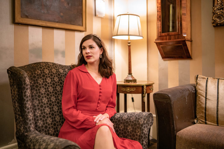 Mode-Bloggerin RetroCat in einem roten Kleid auf einem alten Sessel in einem Hotel in Inverness