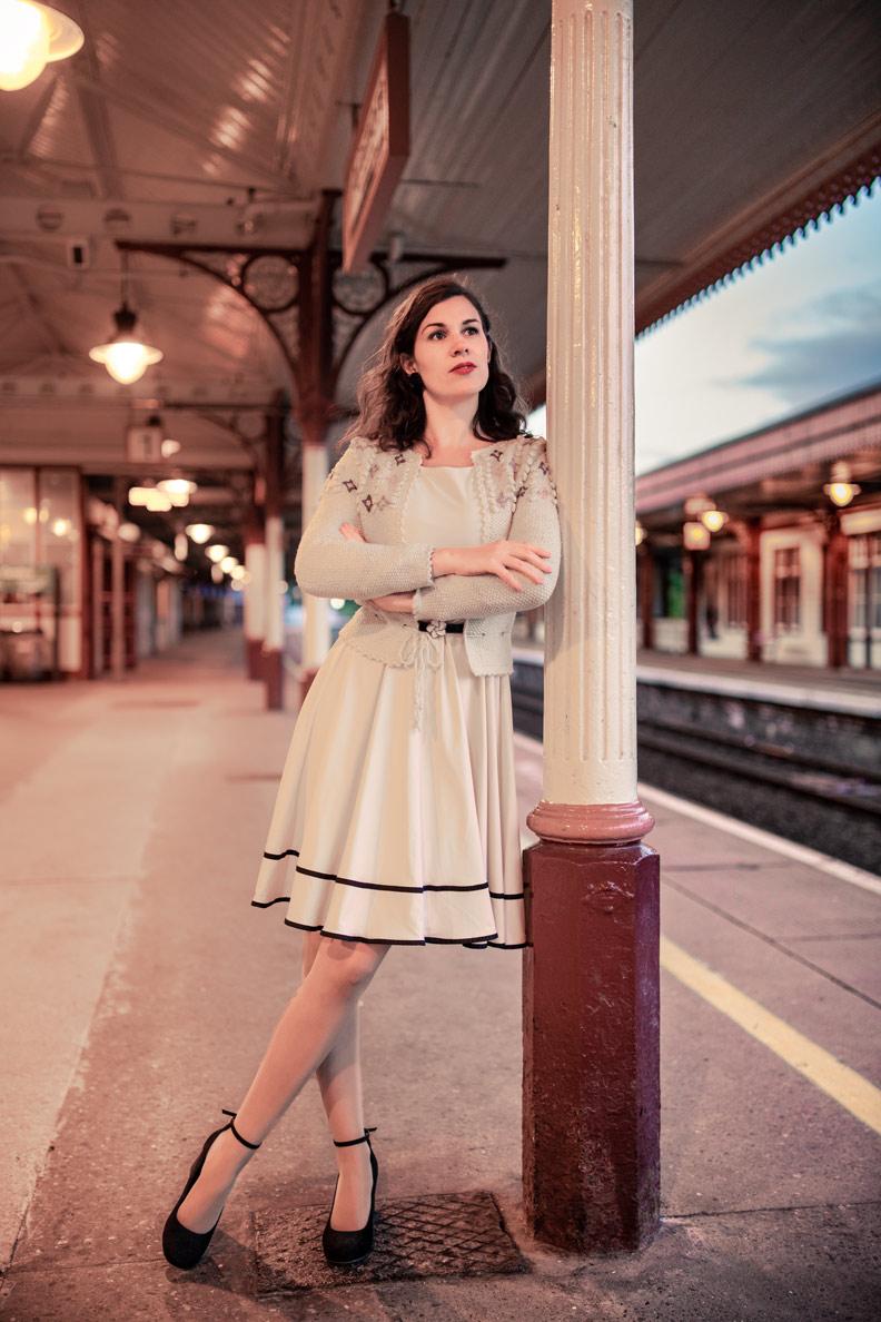RetroCat mit beigem Kleid und 30er-Jahre-Strickjacke am Bahnhof von Aviemore/Schottland