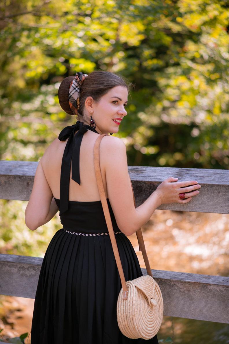 RetroCat mit schwarzem Kleid, Strohtasche und großem Dutt beim Walspaziergang im Spätsommer