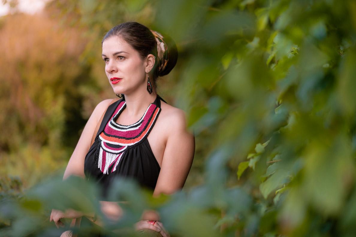 Vintage-Bloggerin RetroCat im grünen Dickicht eines Waldes mit einem Kleid von Lena Hoschek