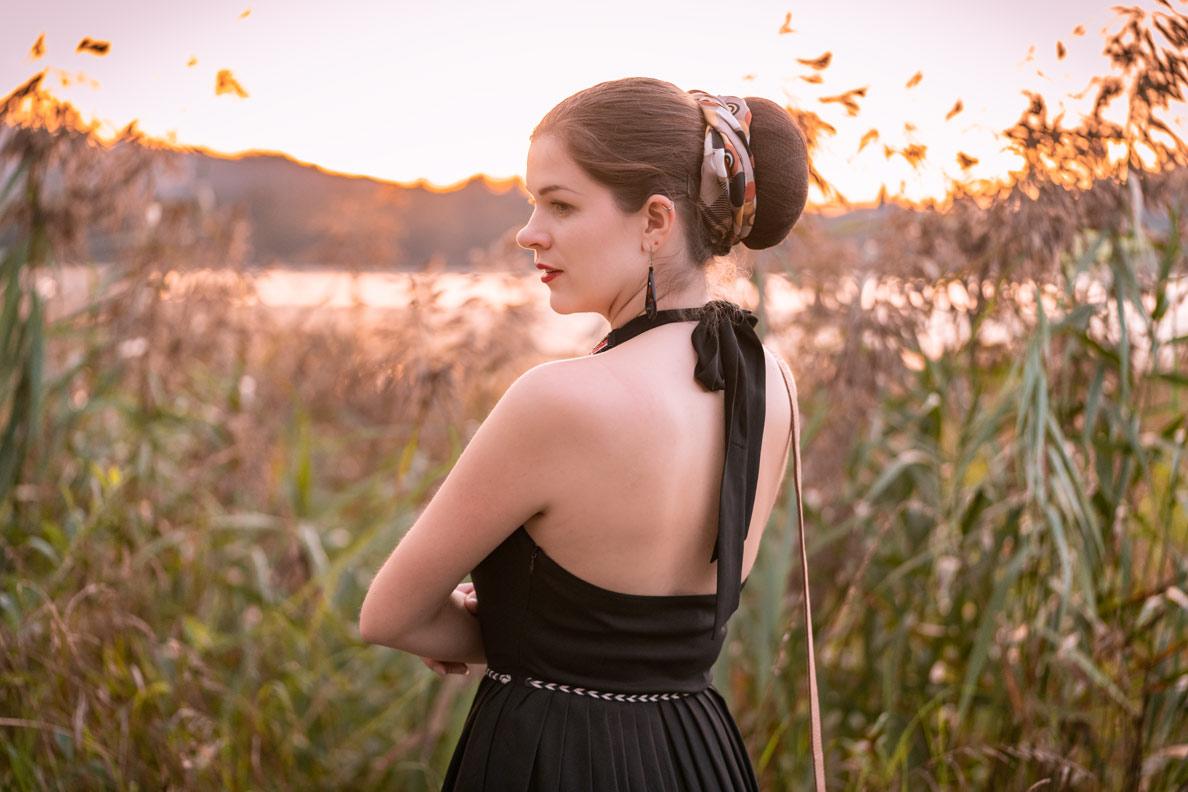 RetroCat mit einem schwarzen Neckholder-Kleid von Lena Hoschek beim Abendspaziergang