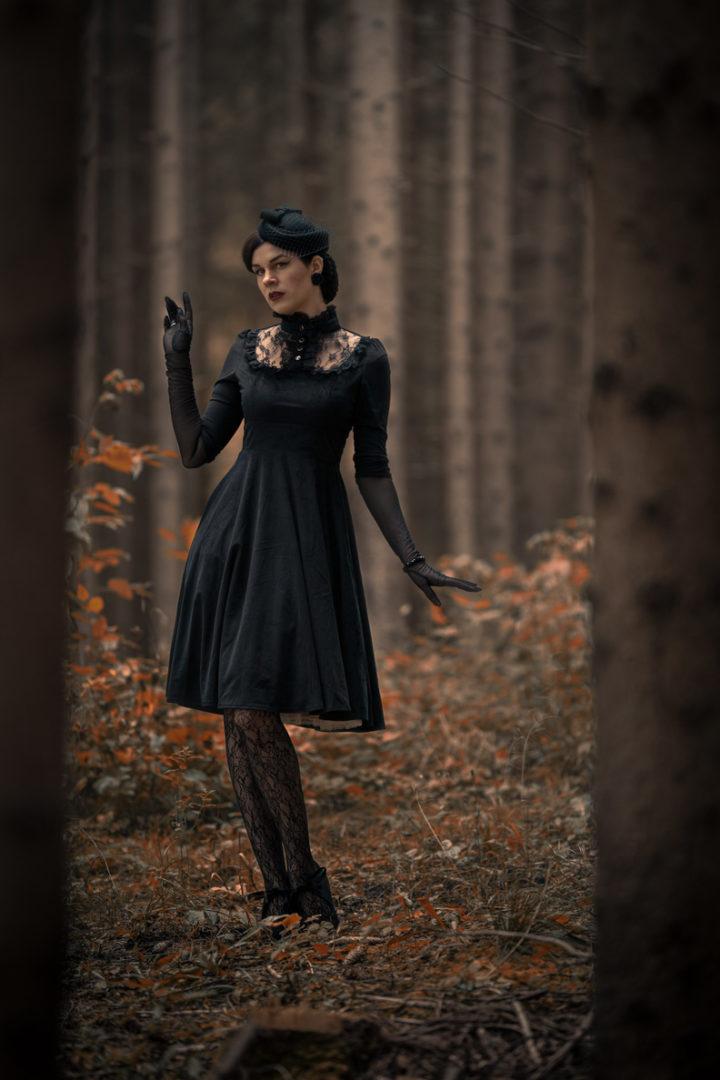 RetroCat in einem düsteren Kleid beim Waldspaziergang