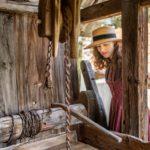 RetroCat blickt in einen alten Brunnen vor einem historischen Bauernhaus