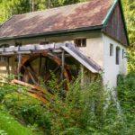 Ein Wasserrad vor einer historischen Mühle