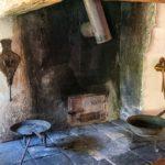 Eine historische Küche mit Feuerstelle und alten Pfannen