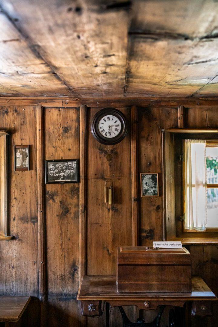 Eine alte Holzwand mit historischer Uhr und Bildern in einem traditionellen Bauernhaus