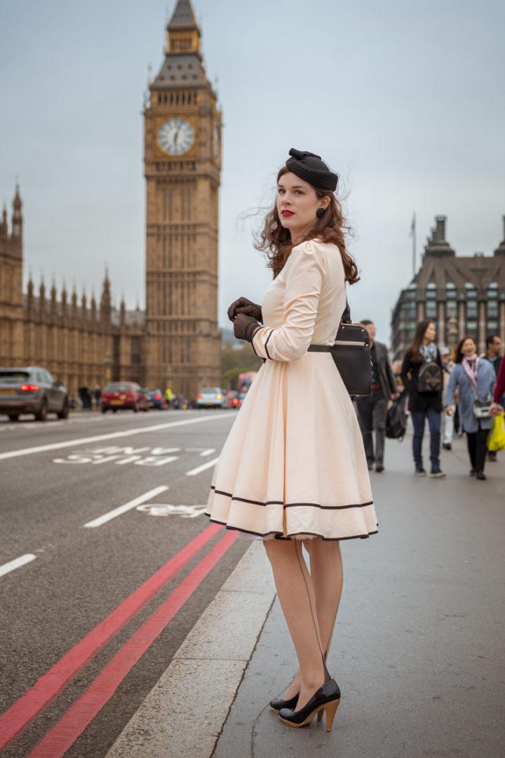 Stilvoll reisen: RetroCat mit beigem Kleid, Strümpfen und Cocktailhut in London