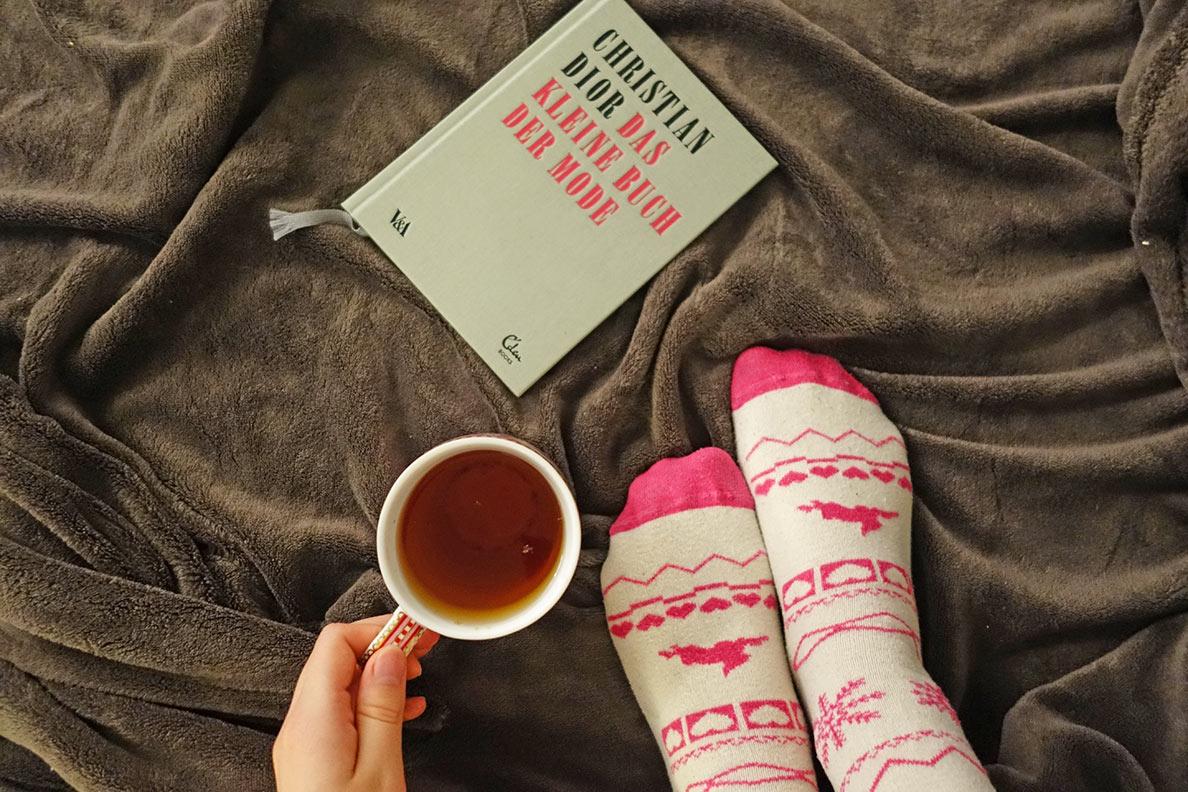 RetroCat mit warmen Socken, einer Tasse Tee und einem Buch im Bett