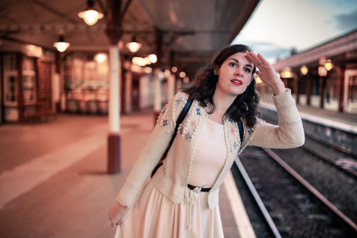 Stilvoll reisen: RetroCat mit Vintage-Strickjacke und beigem Kleid am Bahngleis in Aviemore/Schottland