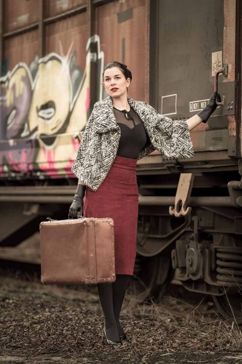 Stilvoll auf Reisen: RetroCat mit einem Vintage-Koffer aus Leder vor einem Zug