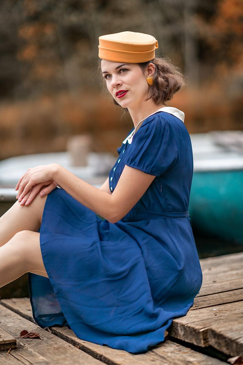 RetroCat mit Pillbox-Hut und blauem Kleid im Stil der 40er-Jare auf einem Steg