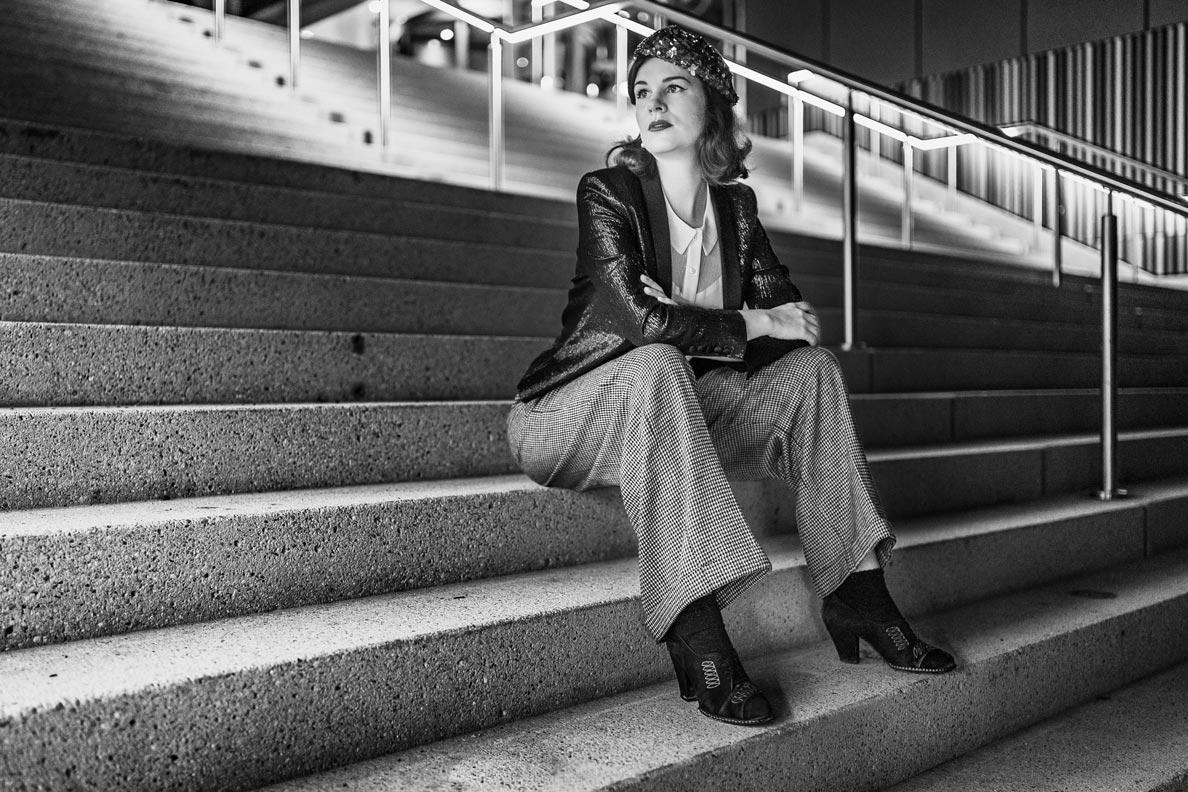 Vintage-Bloggerin RetroCat mit Marlene-Hose und einem eleganten Blazer auf einer Treppe