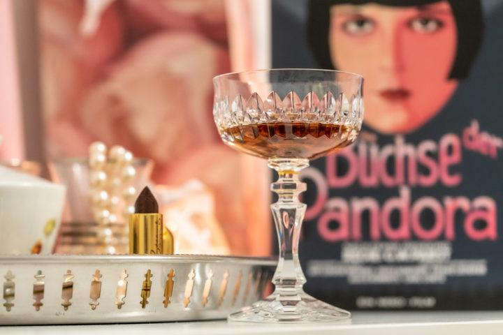 Ein Cocktail in einem Kristallglas vor einer DVD