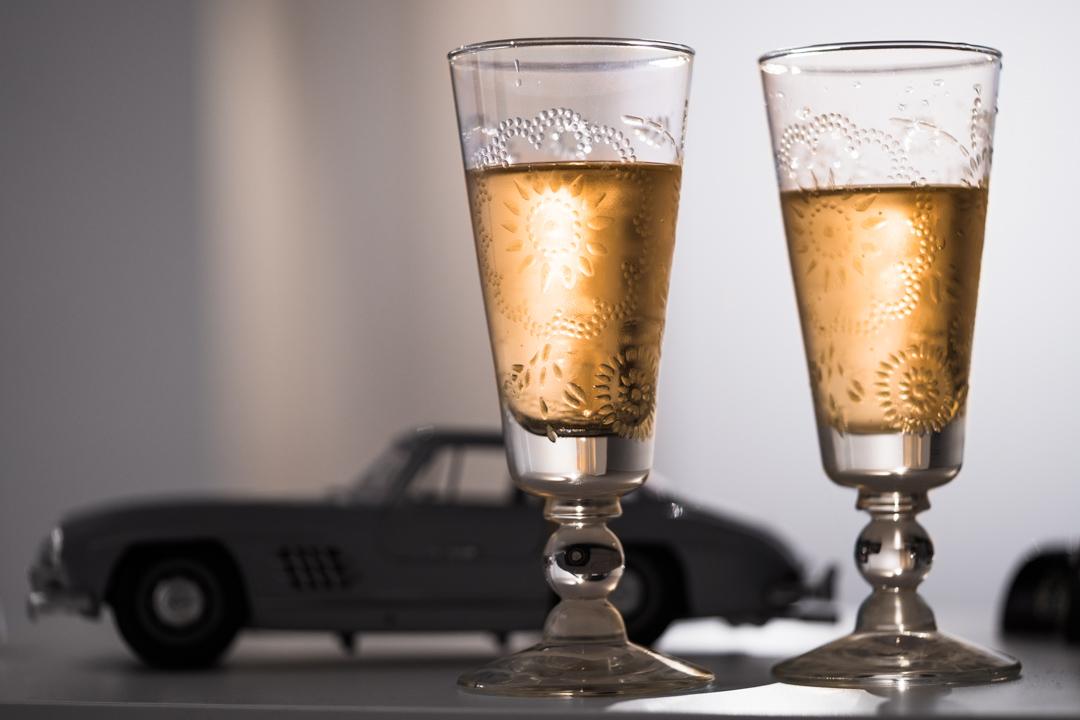 Zwei Gläser Sekt vor einem Modellauto