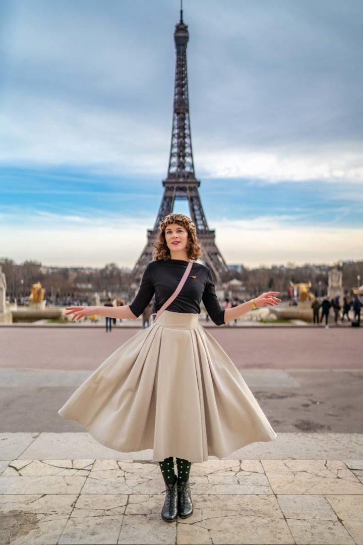 RetroCat mit einem beigen Rock im New Look vor dem Eiffelturm in Paris