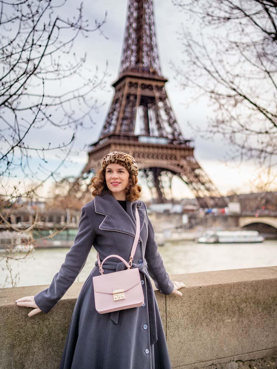RetroCat mit einem grauen Retro-Mantel vor dem Eiffelturm in Paris