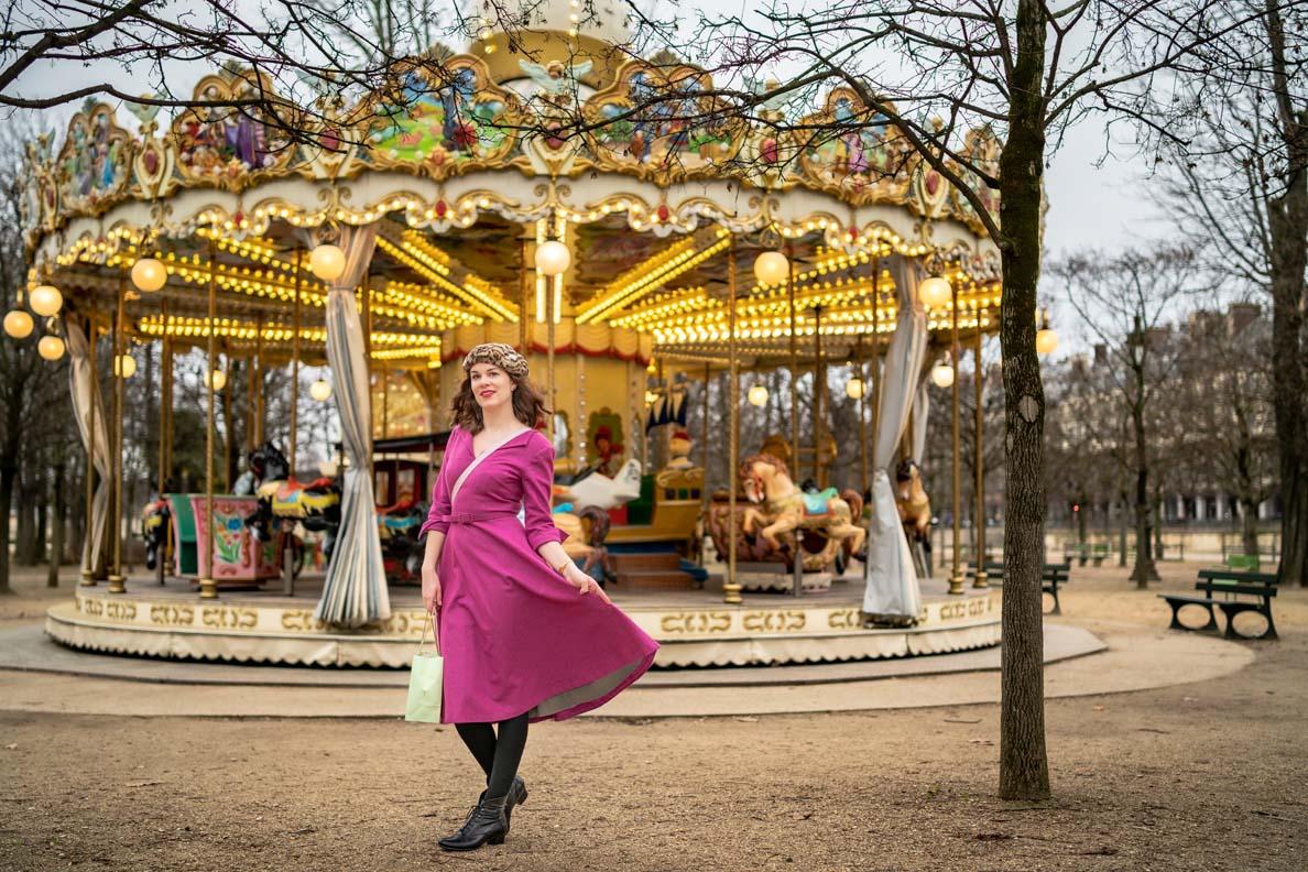 RetroCat mit pinkem Kleid vor einem Karussell in einem Pariser Park
