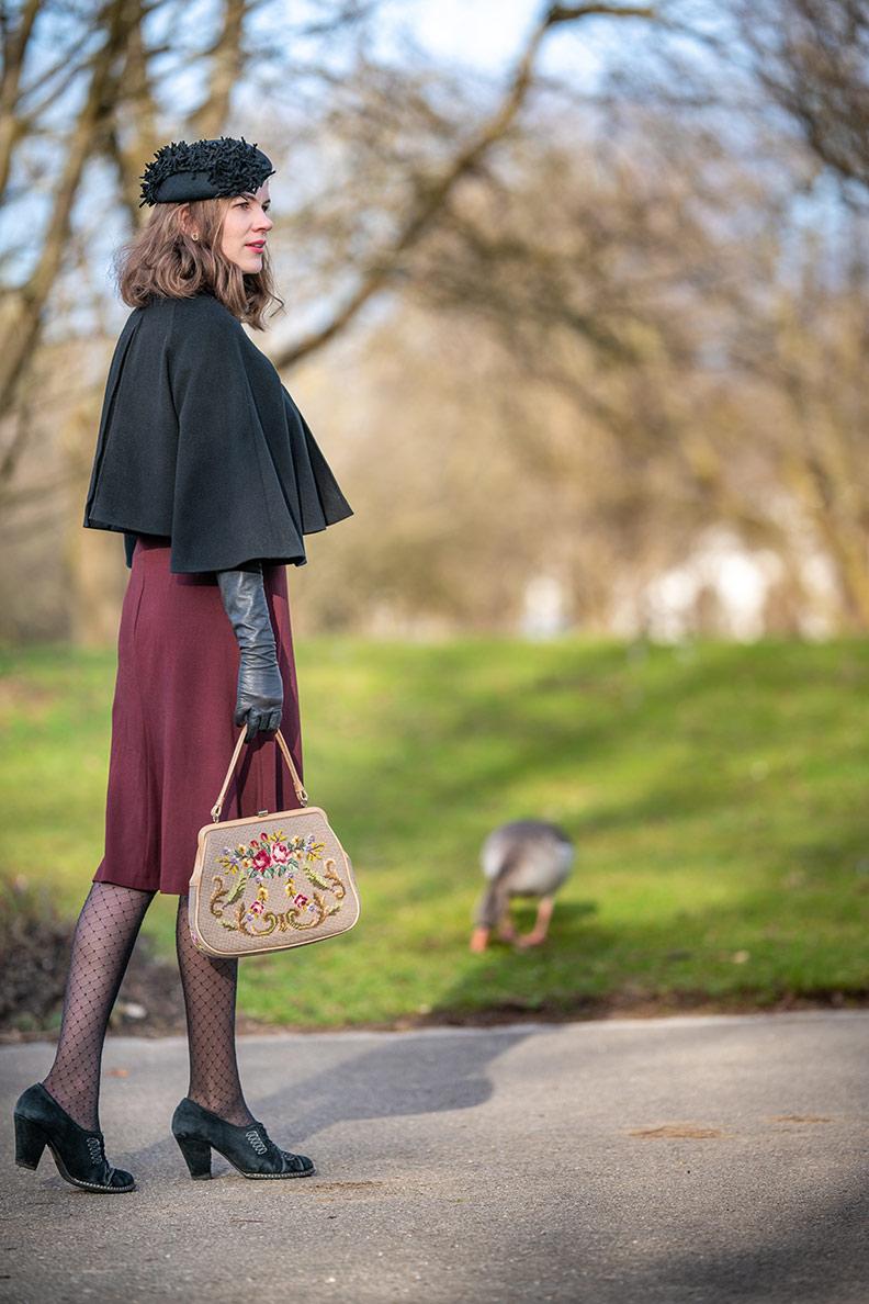 RetroCat mit einem Retro-Kleid, Vintage-Jacke und langen Lederhandschuhen im Park