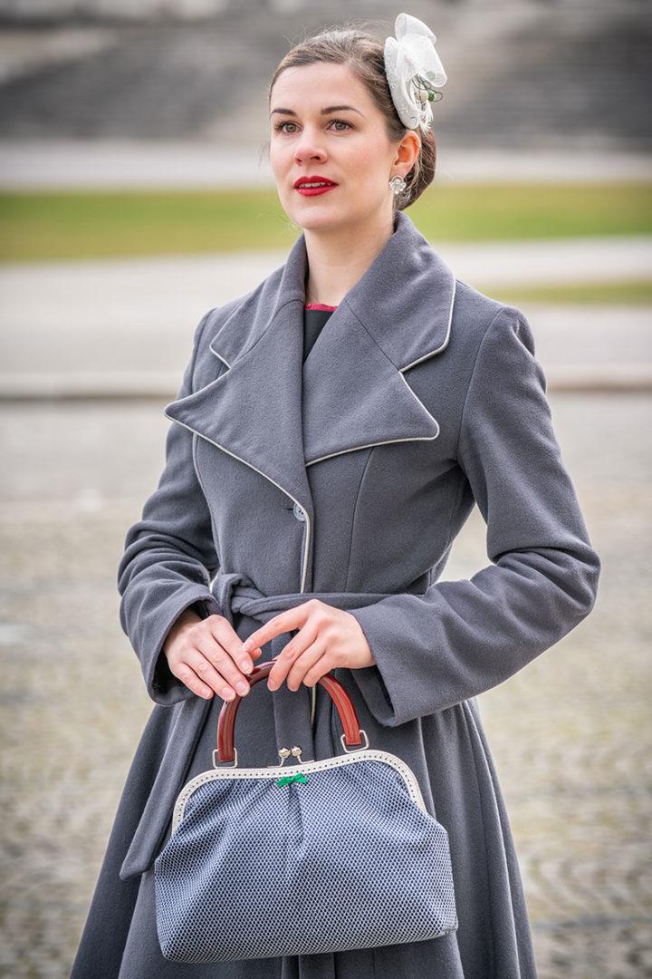RetroCat mit einem weißen Fascinator und einer passenden Retro-Handtasche von Nadja Christner