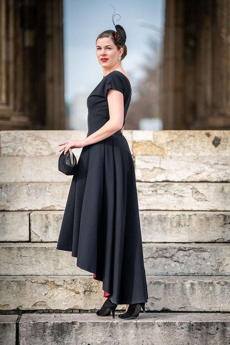 RetroCat mit einem eleganten Abendkleid von Ginger Jackie, Handtasche und Fascinator