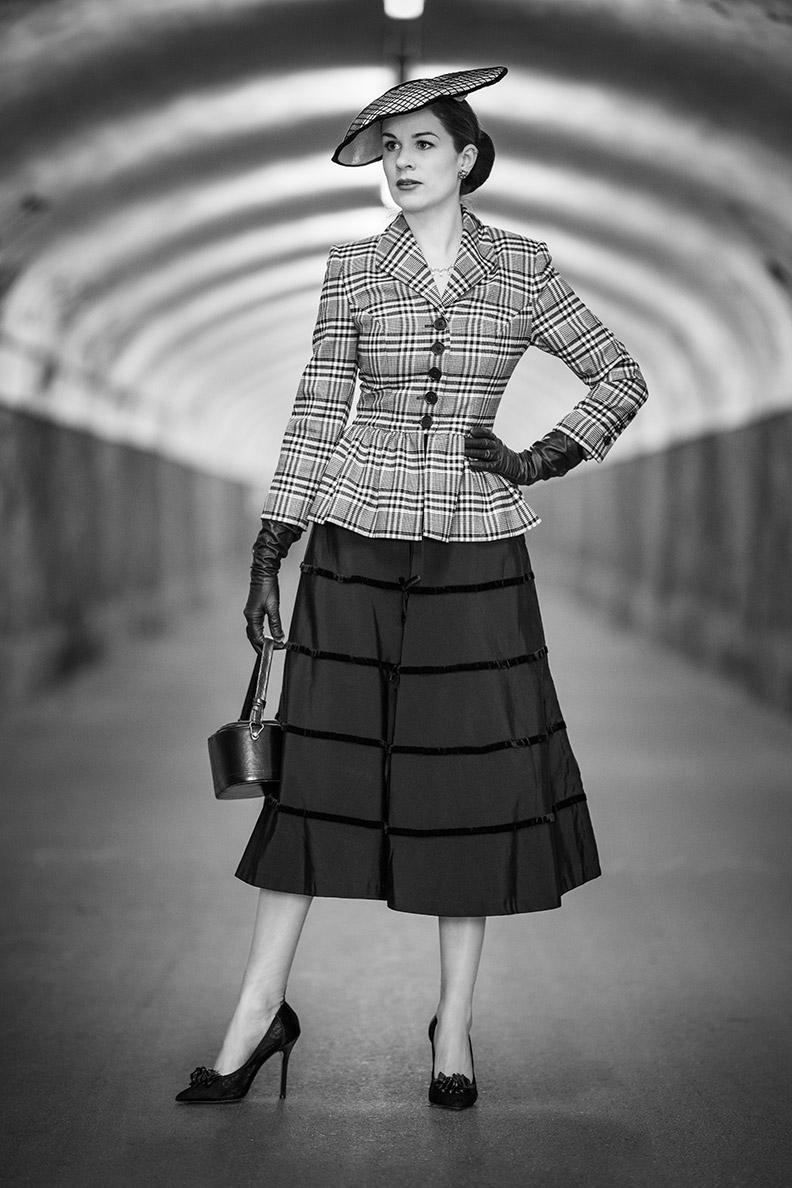 RetroCat mit einem schwarzen Midi-Skirt aus den 1950ern und Karo-Blazer