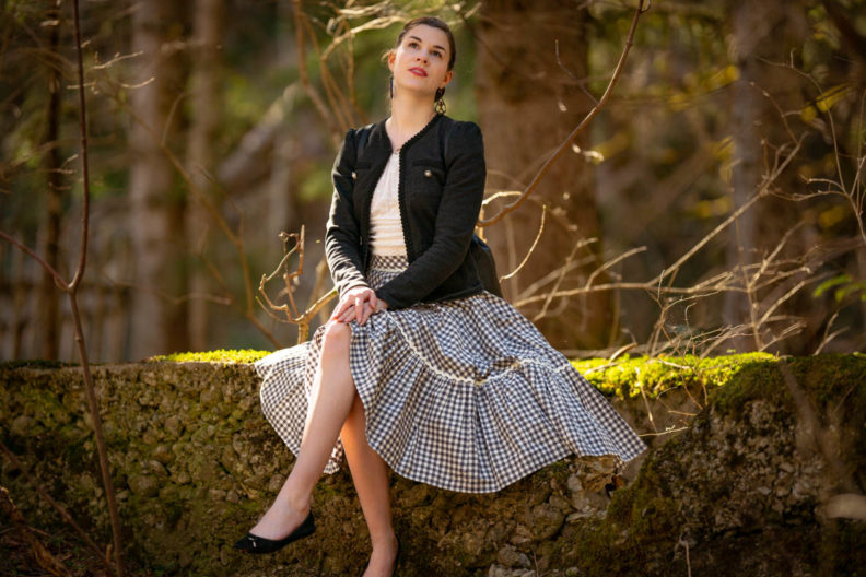 RetroCat wearing a romantic top, jacket, and plaid skirt in the forest