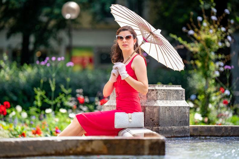 RetroCat mit einem korallfarbenen Kleid von Miss Candyfloss an einem Brunnen in München