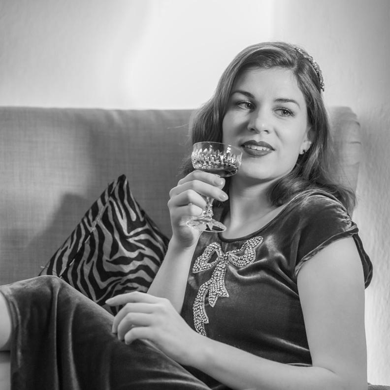 RetroCat mit 20er-Jahre-Outfit beim Cocktail-Trinken