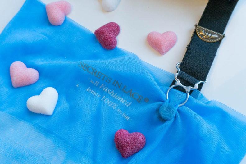 A garter belt on a blue nylon stocking