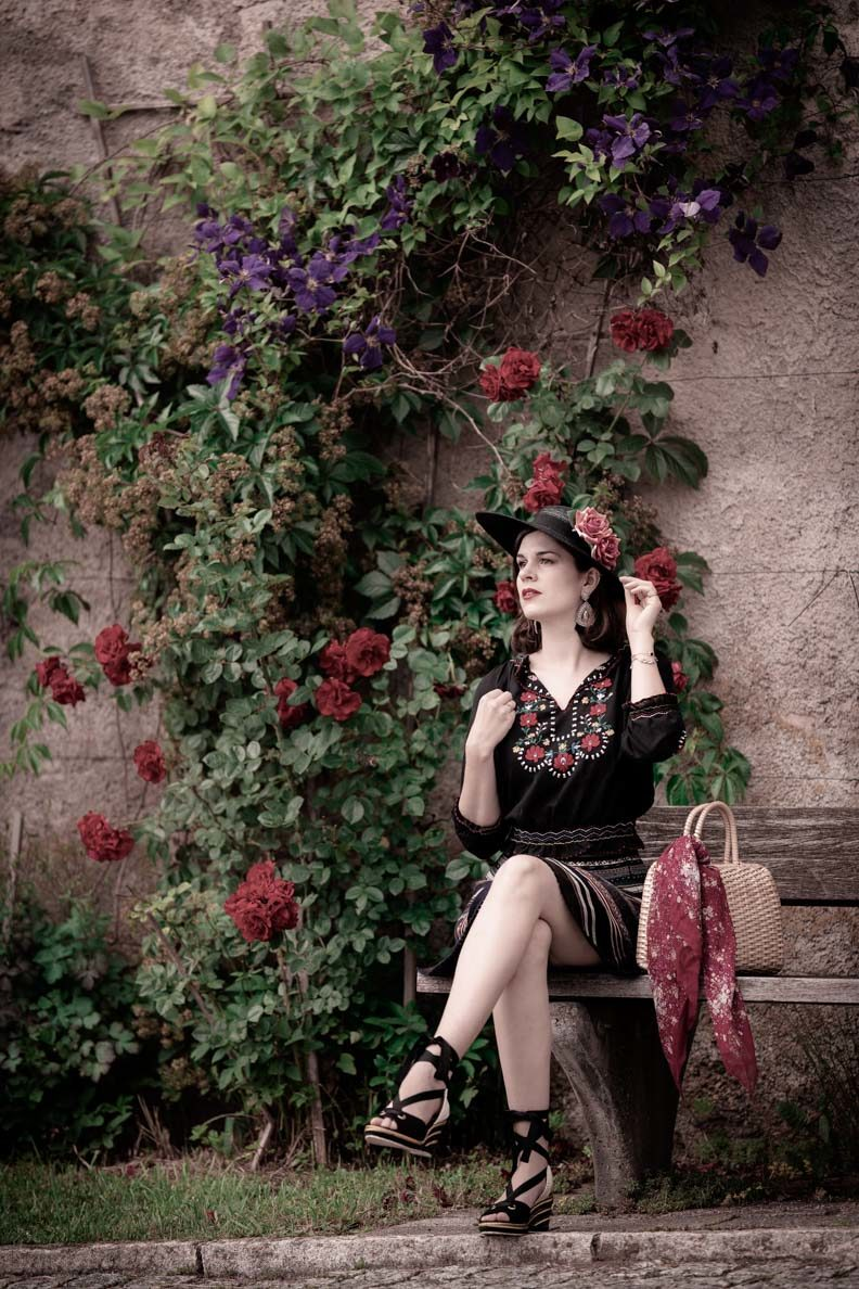 RetroCat with a ribbon skirt and Hungarian blouse in front of a rose wall