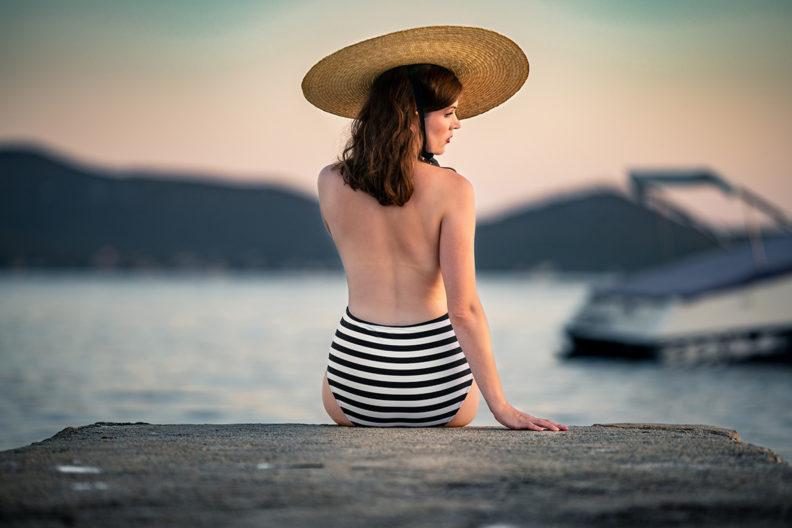 RetroCat wearing a striped swimsuit with a deep back neckline